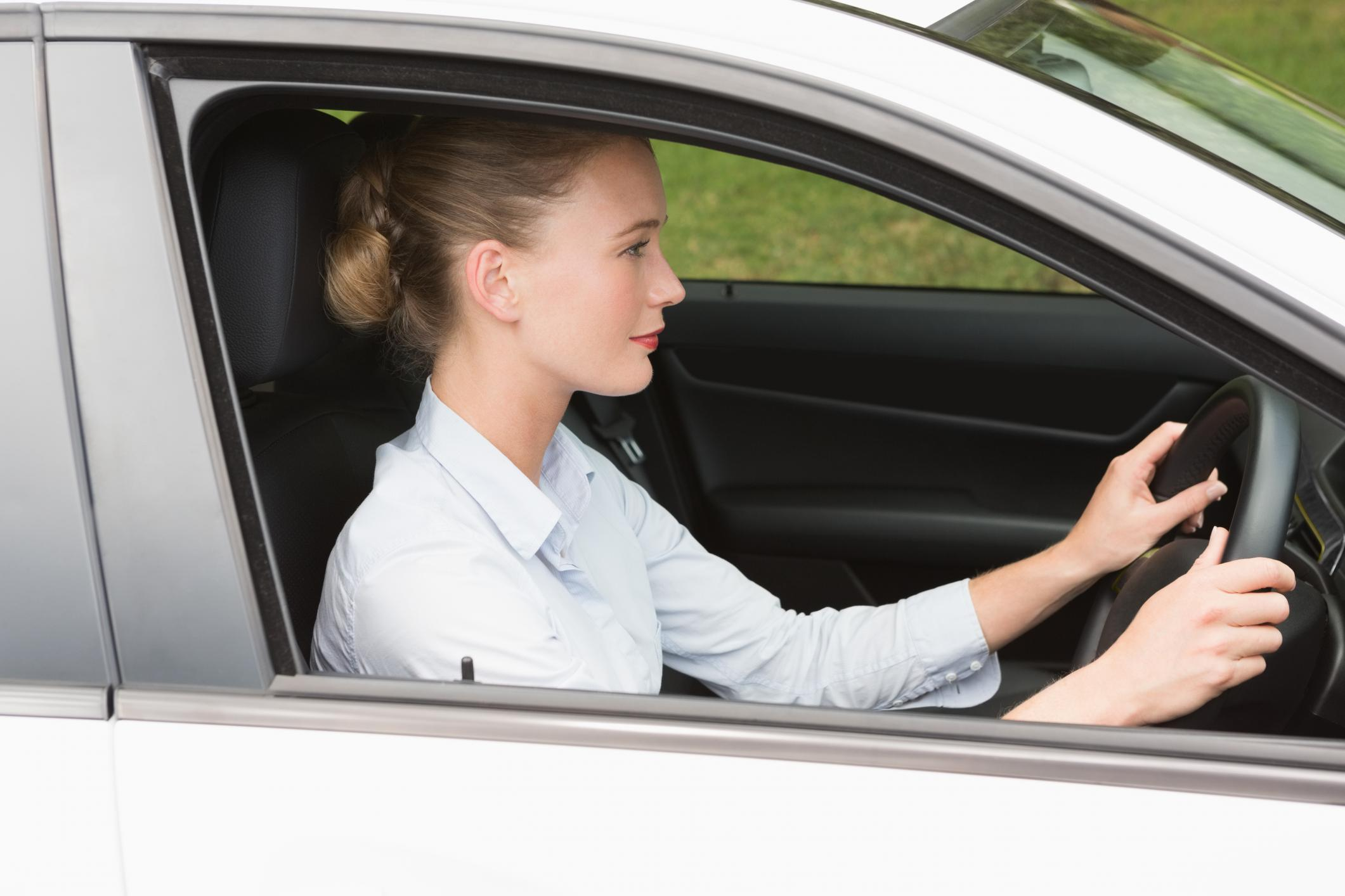 Young Woman Driving Car and Holding Steering Wheel